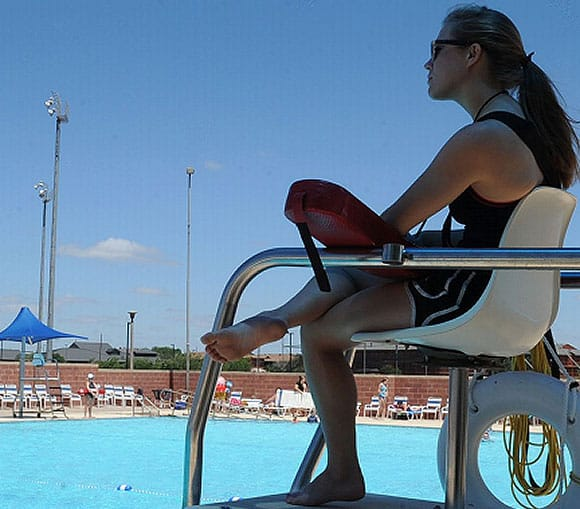 Young Angle women sitting in a lifeguard chair watching people in a pool.