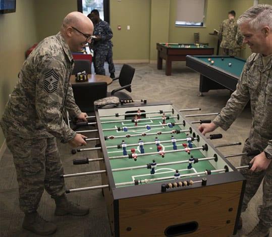 Two airmen playing foosball
