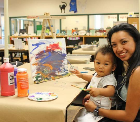 Mother and toddler painting a picture on canvas