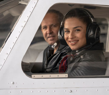 Woman and instructor looking out of the window of the cockpit