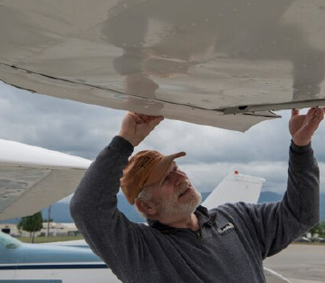 Man inspecting a small airplane