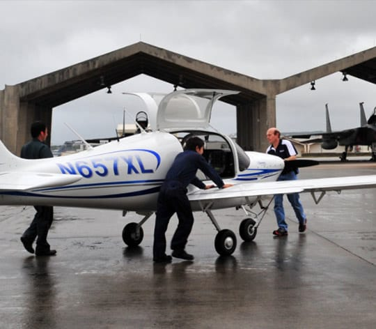 Three people getting a small plane ready