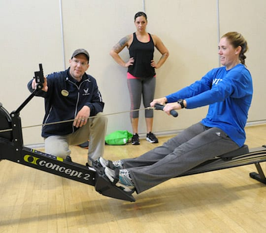 Female on a rowing machine with physical fitness trainer showing her how to properly use the equipment