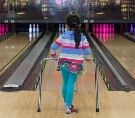 Little girl using a bowling tool for beginners