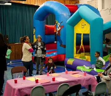 Children and adults at an indoor bouncy house