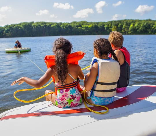 girls sitting on a paddle board looking at the lake