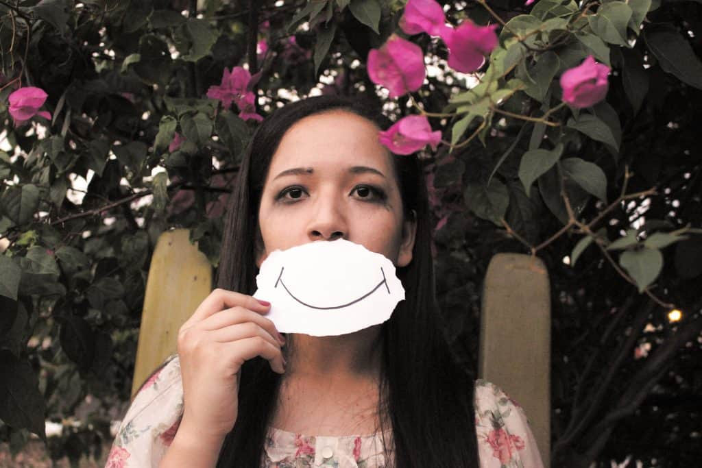 Women looking happy holding a sad card board smiley face in front of her mouth