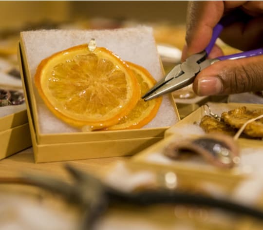 Person showing an orange that is a piece of jewelry