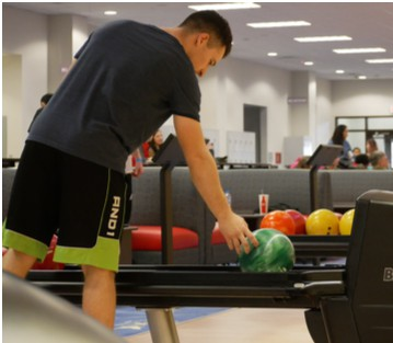 Person picking up a bowling ball and is ready to play