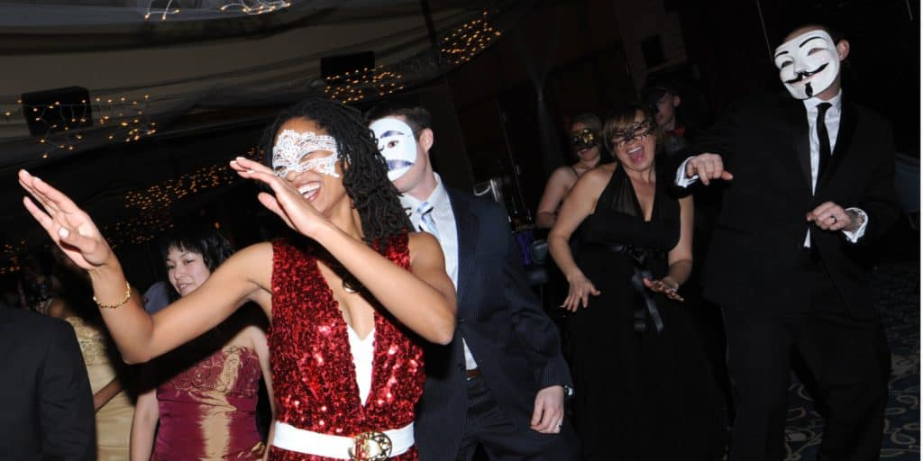 A group of people wearing costume masks , dancing at an Air Force Club
