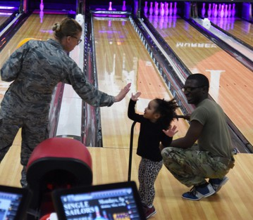 Two Airmen with a child high 5ing each other at a bowling center