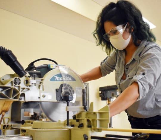 Women cutting wood on an electric saw