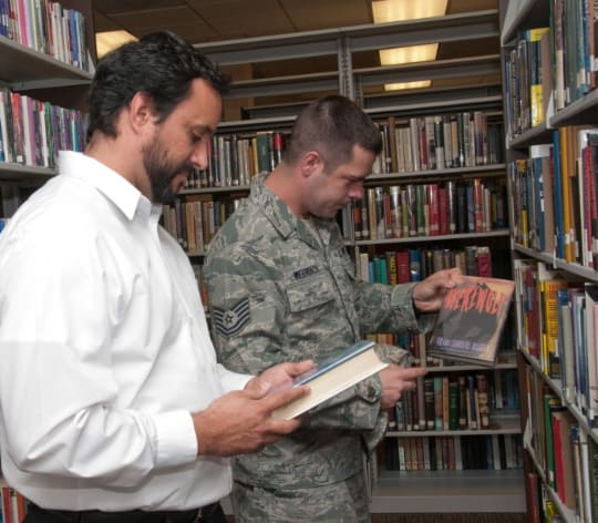 Airmen and civilian man at the library looking at books