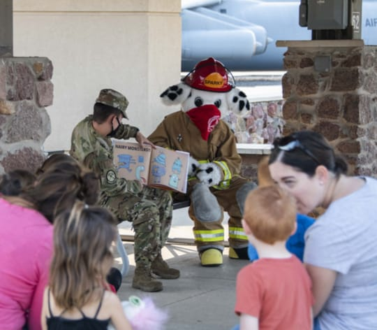 Mr.Sparky and Airmen reading a book to children and their parents
