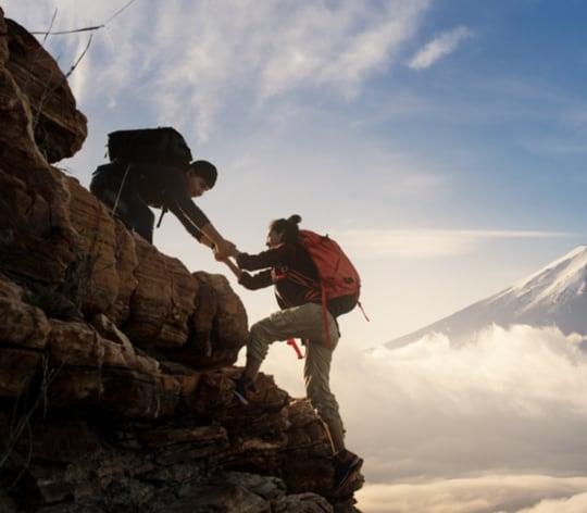 two hikers climbing a mountain