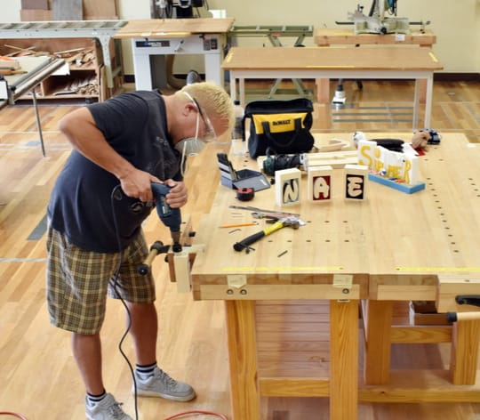 Men working on a woodworking bench