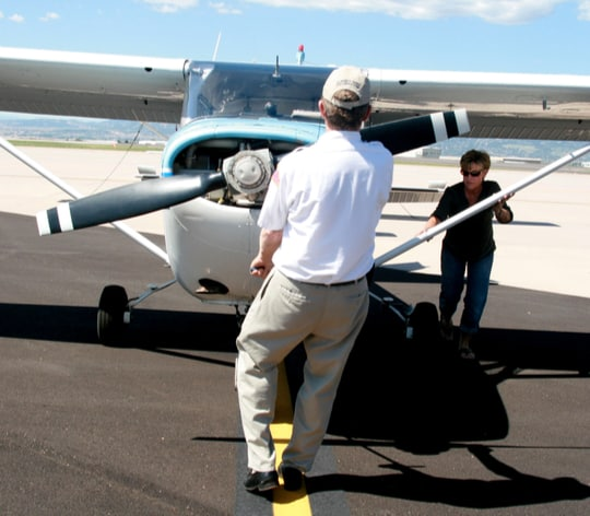 Husband and wife getting plane ready to fly