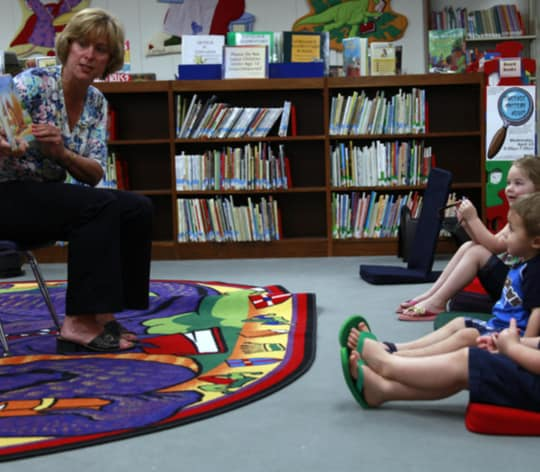Librarian sharing a story with small children who are sitting on the floor