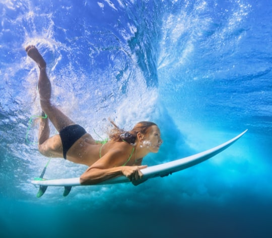 Womesurfing and is under water with surfboard